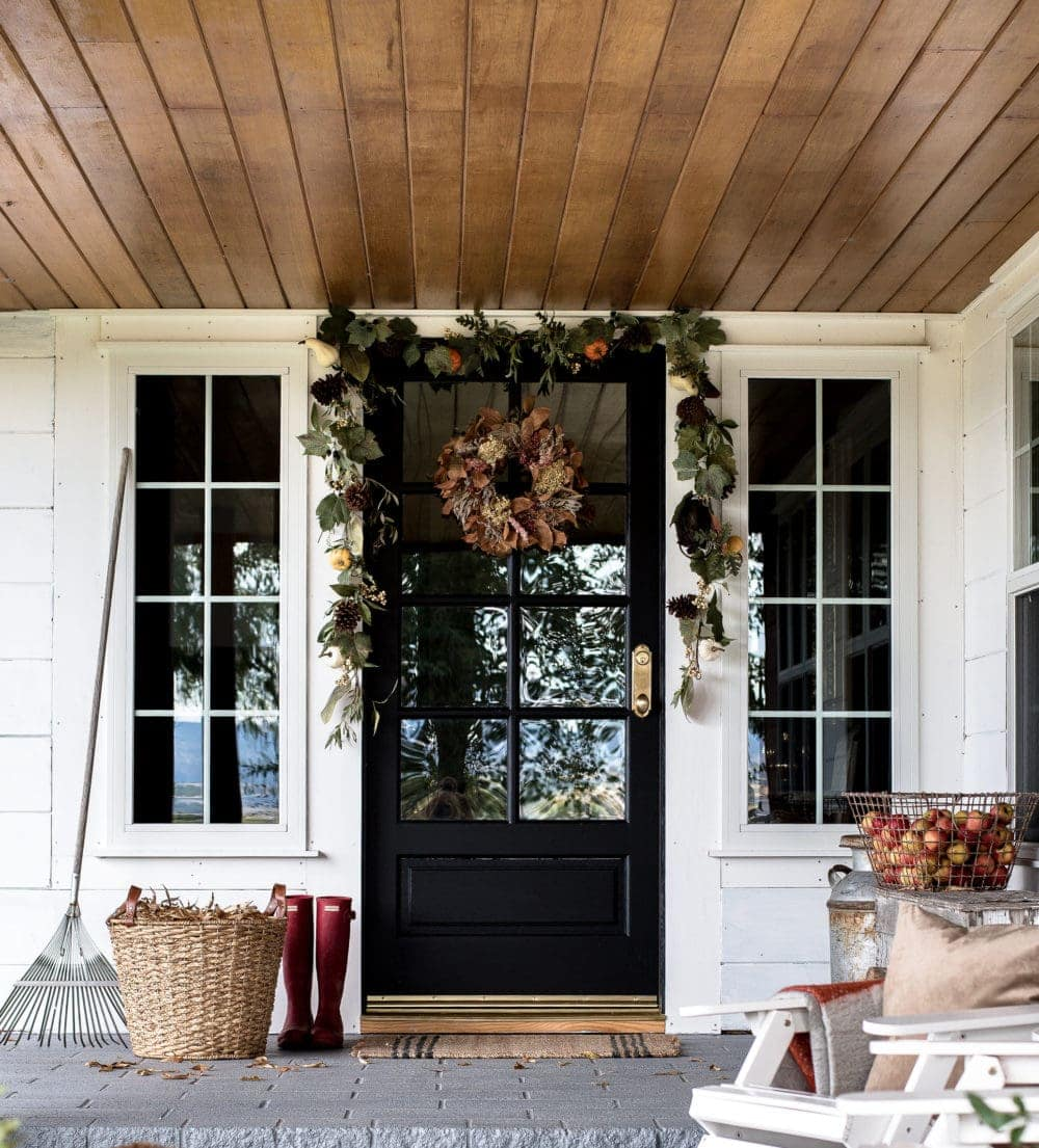 Fall front porch ideas using a basket of dried leaves next to a rake, a basket of apples, and a green garland over the door