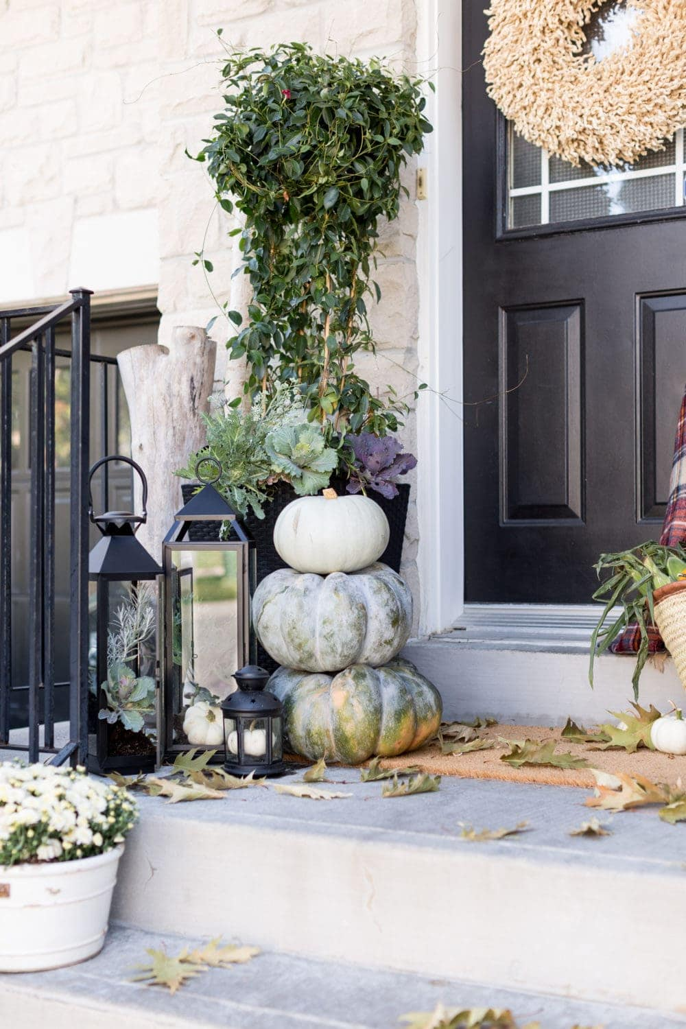 Fall front porch ideas using black lanterns and stacked pumpkins