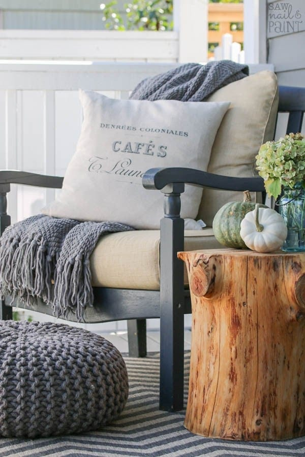 Fall front porch ideas using a blanket and throw pillow on a chair next to an old stump used as a side table