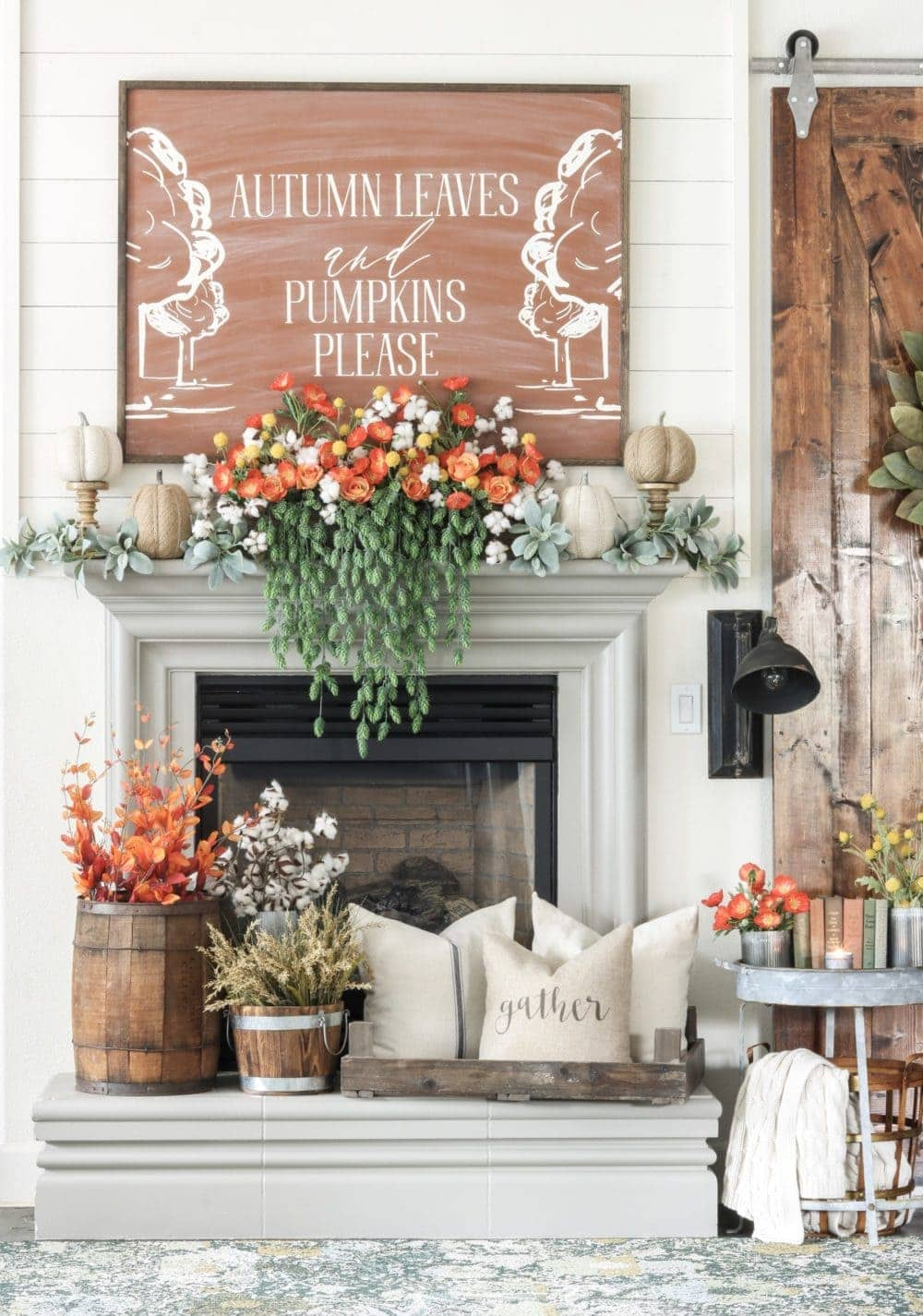 Fall mantel ideas using orange florals, wooden barrels, and cozy pillows centered under a giant piece of artwork
