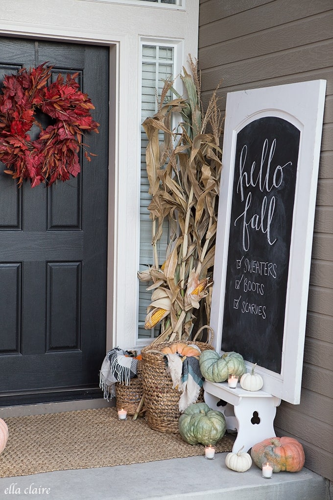 Fall front porch ideas using a red wreath, corn stalks and a chalkboard sign