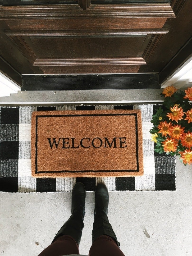 Fall front porch ideas with a jute welcome doormat layered over a black and white checkered doormat