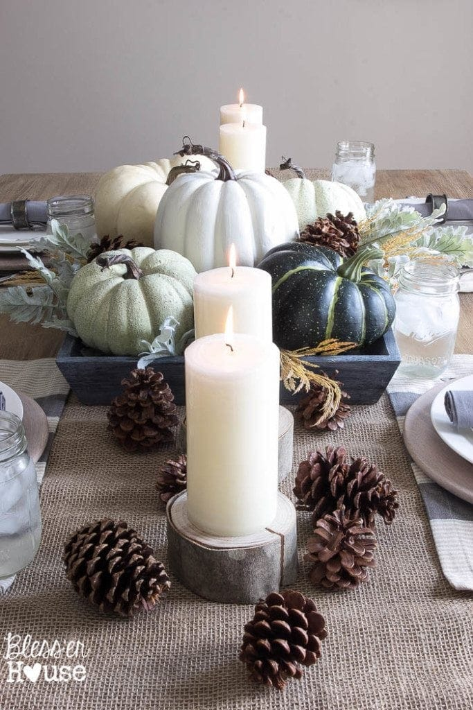 Thanksgiving table centerpieces with green and blue pumpkins and pinecones along a jute runner