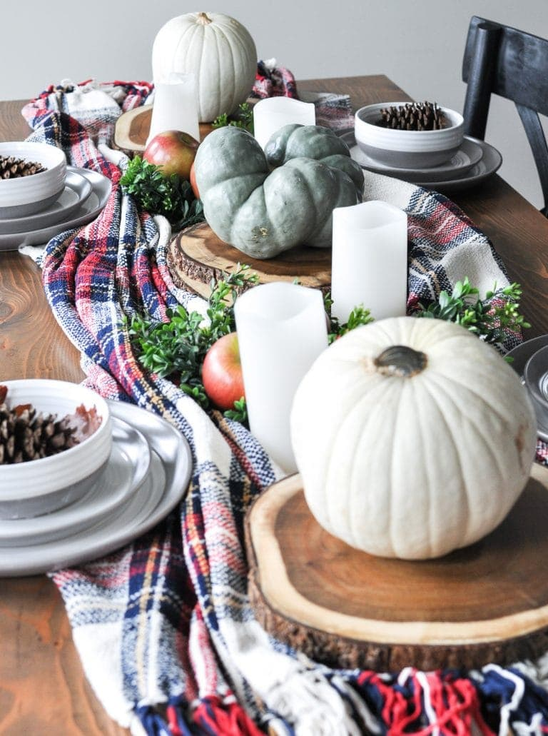 Thanksgiving table centerpieces using a plaid runner, tree slices and white pumpkins