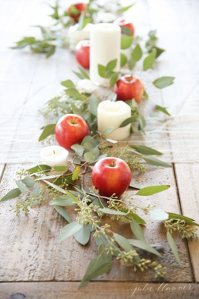 Thanksgiving table centerpieces using eucalyptus runner and apples and candles