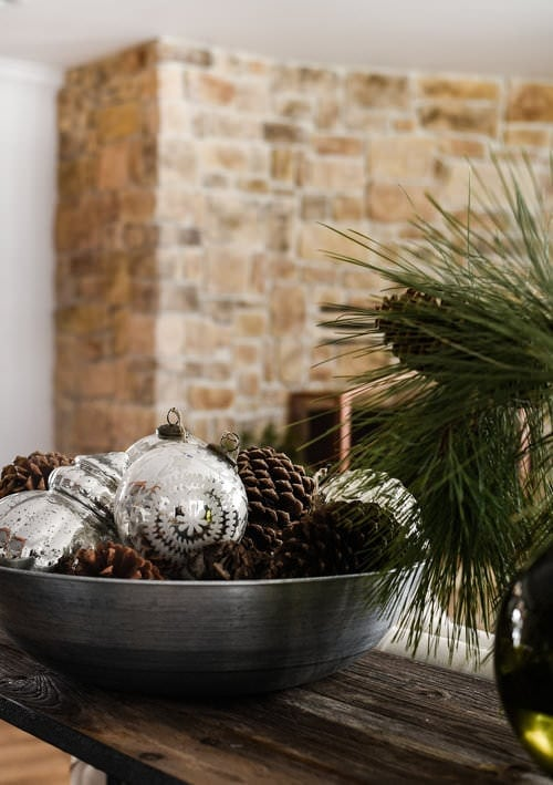 minimalist christmas decorations using ornaments and pine cones in a bowl