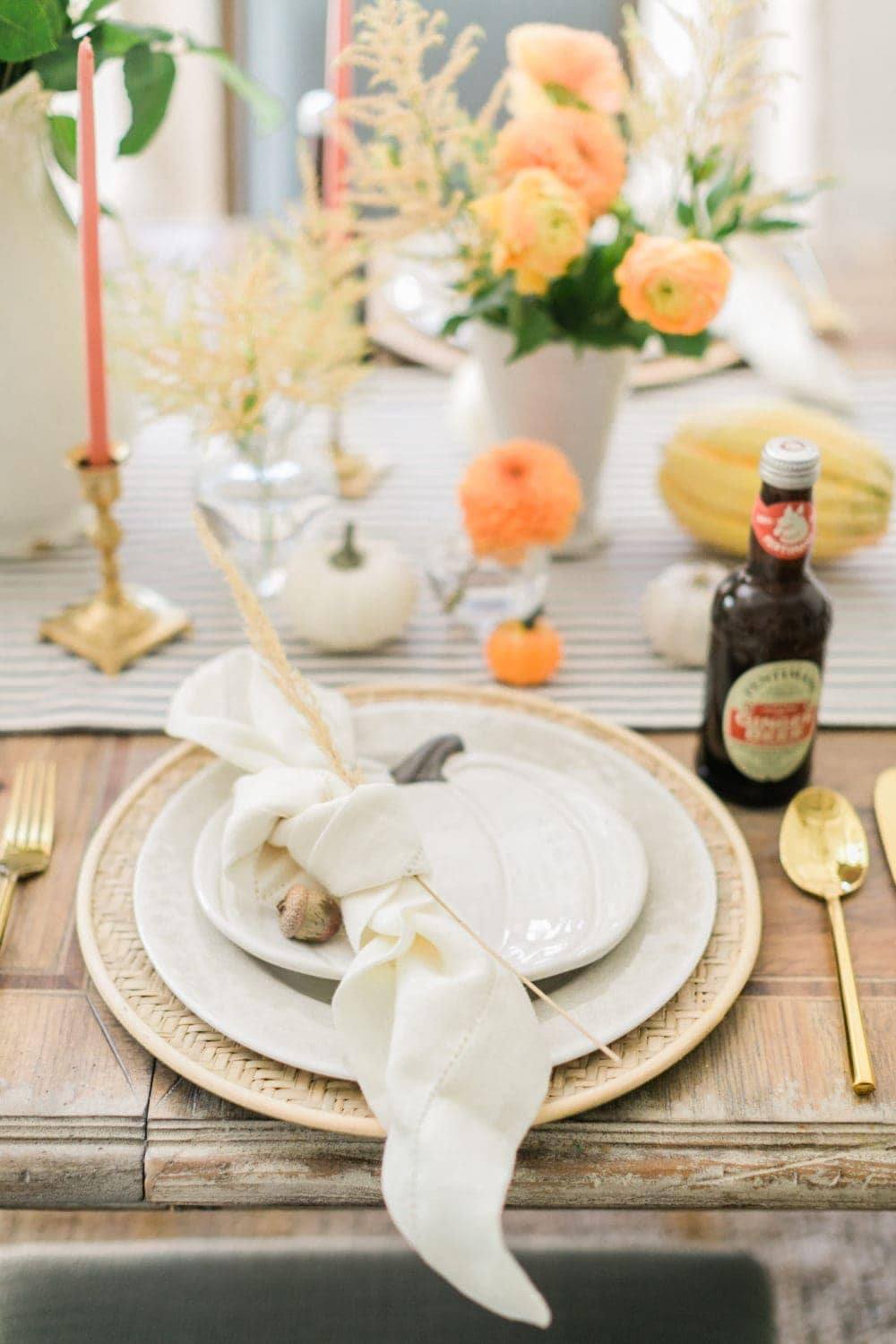Thanksgiving table centerpieces with mini pumpkins, gold candleholders and white napkins tied with a wheatstock