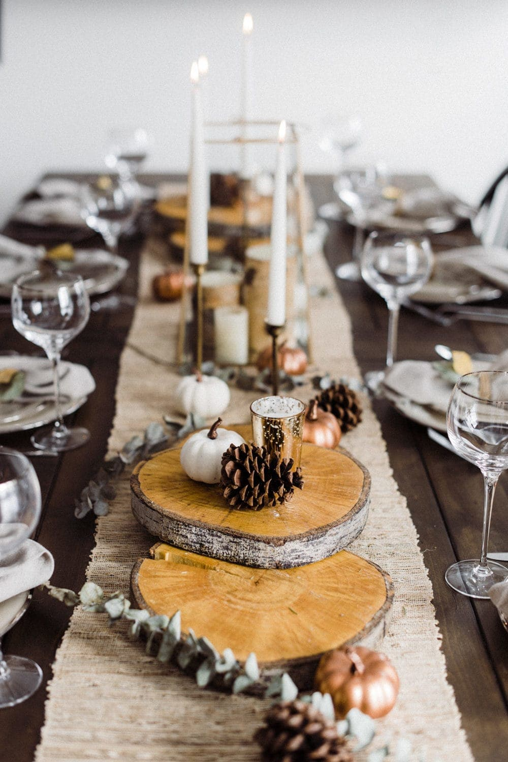 Thanksgiving table centerpieces with a jute table runner, round tree slices and vintage brass candlesticks