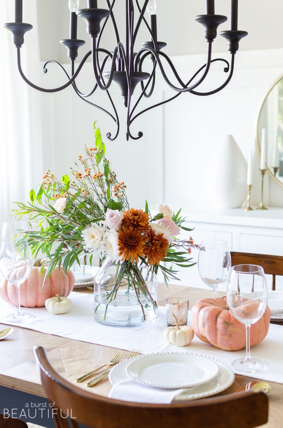 Thanksgiving table centerpieces with a fall floral arrangement and orange pumpkins