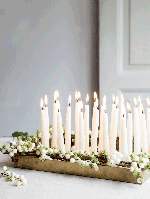 minimalist christmas decorations using a grouping of candles and a gold tray