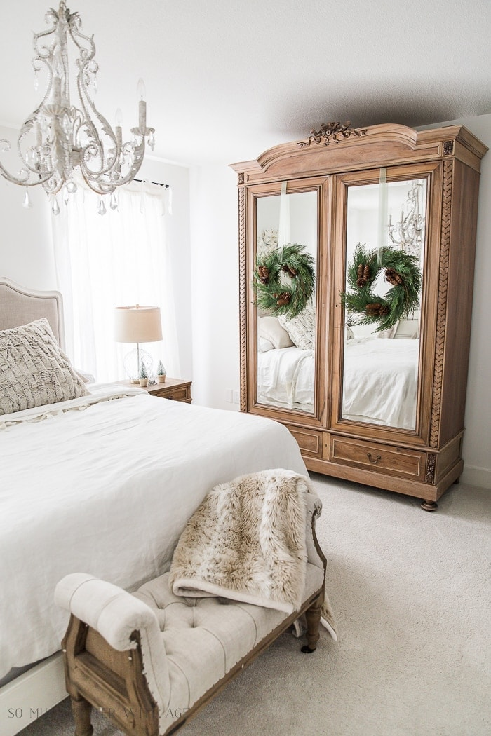 minimalist christmas decorations using two wreaths hung on an armoire