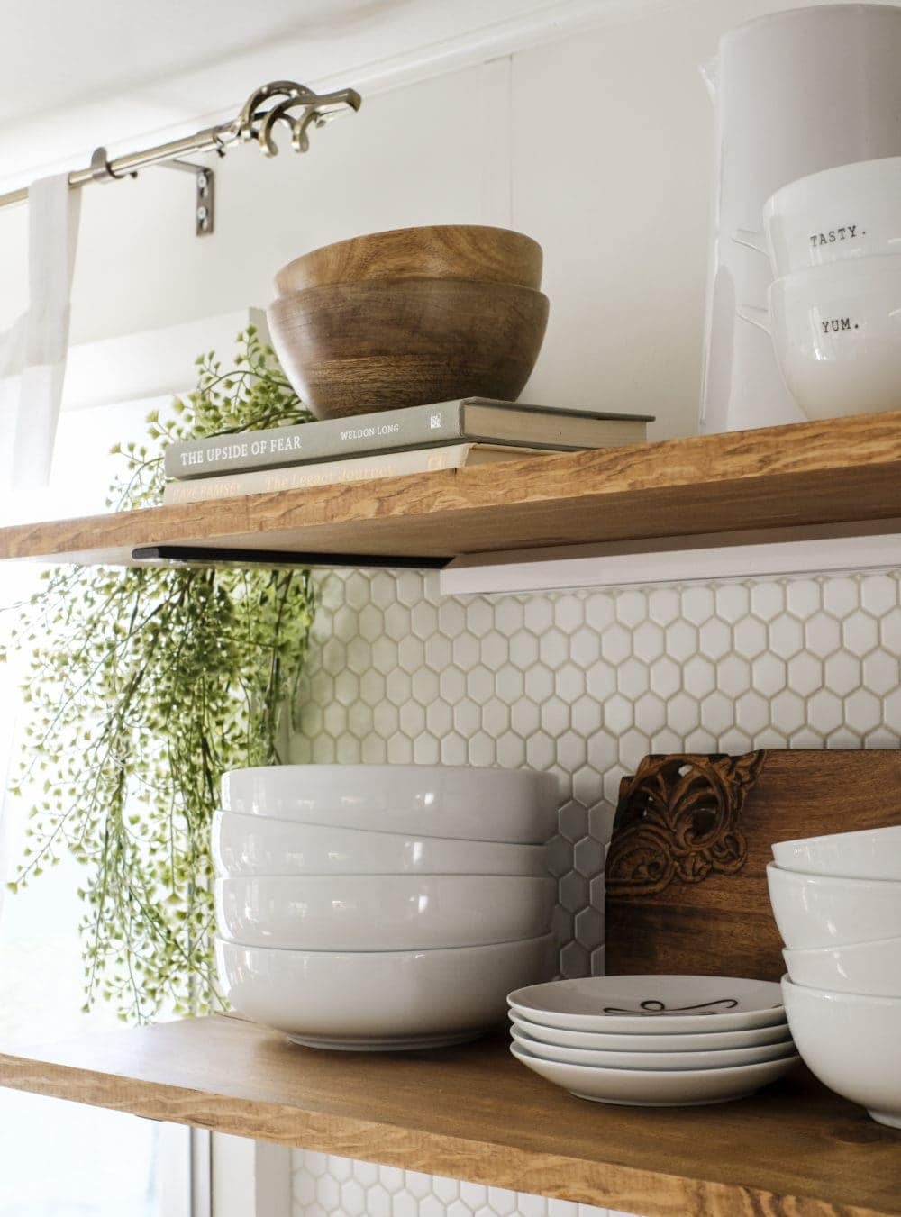 Open shelving with stacked bowls and cascading greenery