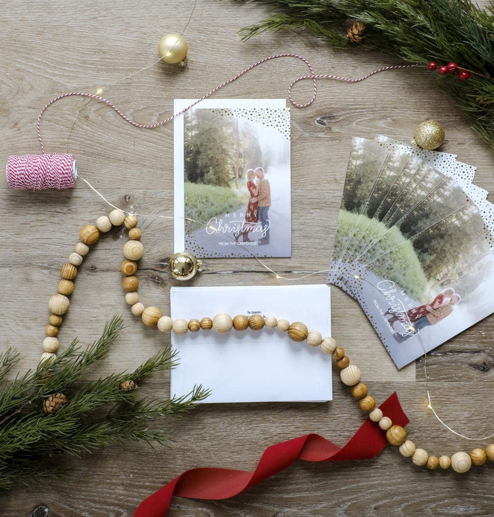 Overhead view of a personalized Christmas card layed out with ribbon, garland, and greenery