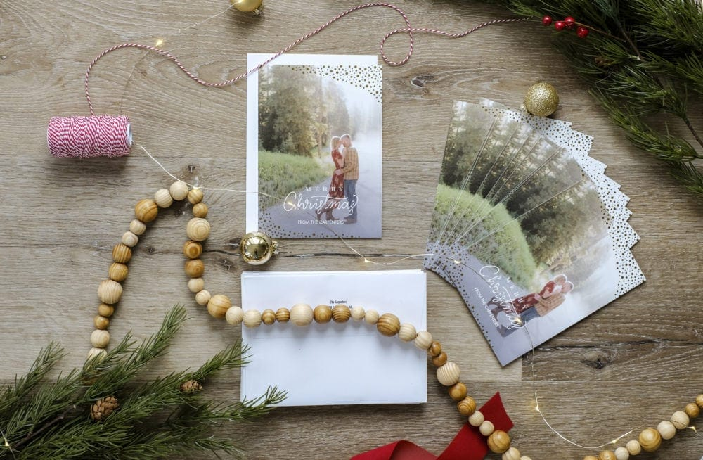 Personalized Christmas cards layed out next to envelopes surrounded by ribbon, garland and greenery