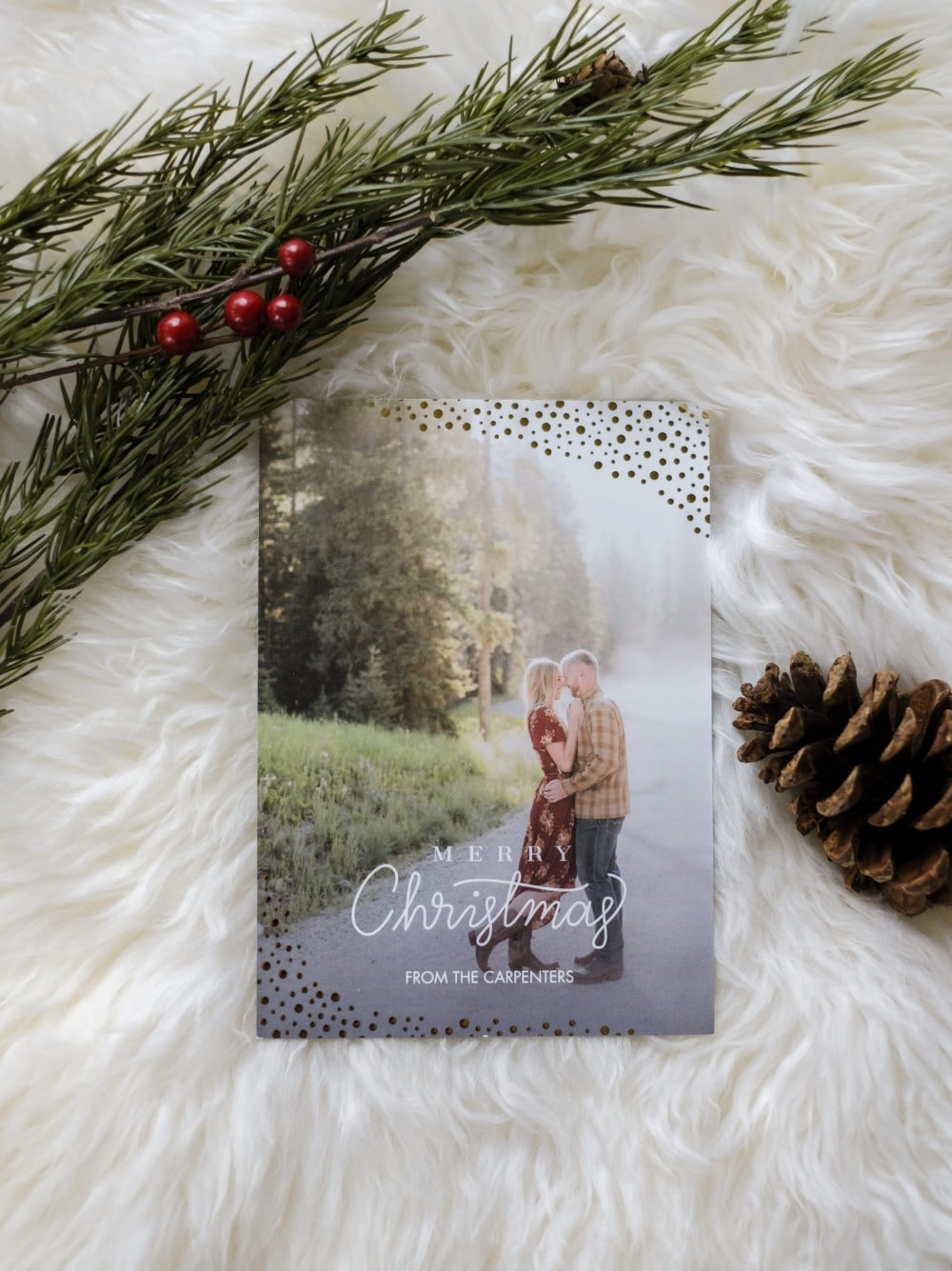 A personalized Christmas card laying on a white sheepskin rug next to greenery and a pinecone
