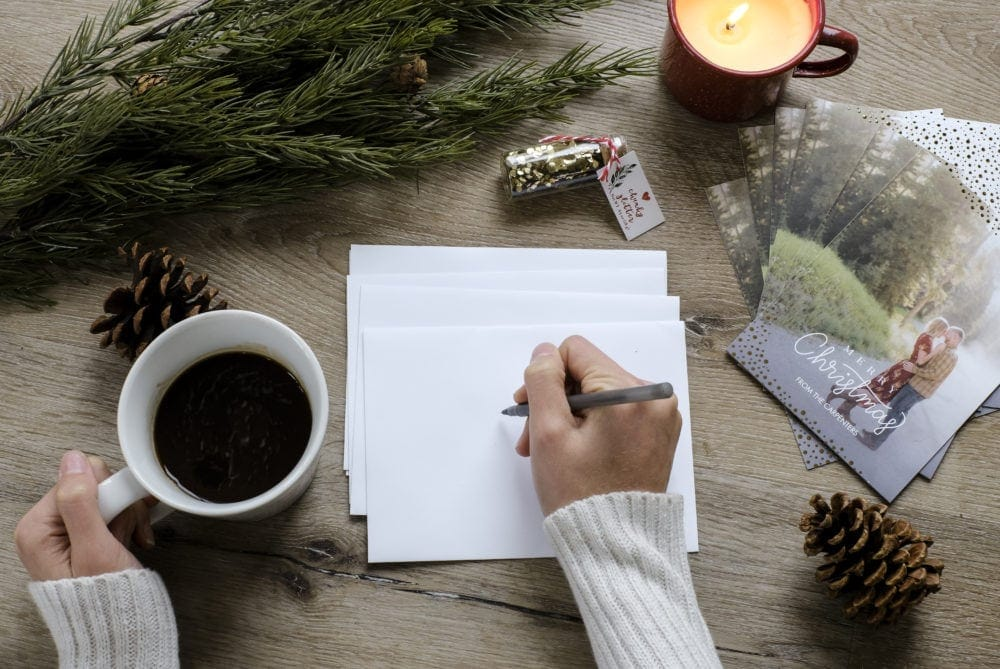 Overhead view of someone addressing envelopes next to a stack of personalized Christmas cards holding a coffee