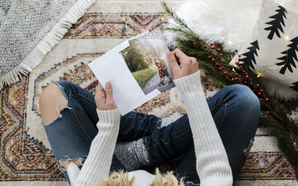 A woman sitting on the floor putting a personalized Christmas card into an envelope