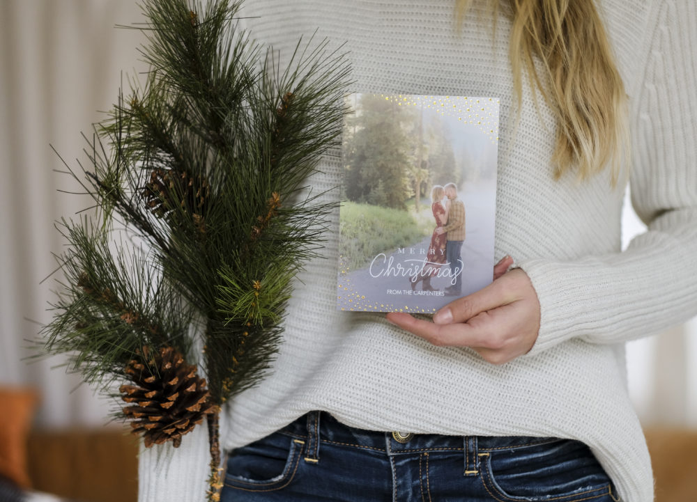 Woman holding a Christmas card photo and a pine tree branch