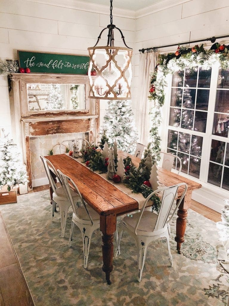 Chrismtas dining room lit up with twinkle lights and a table runner made from garland and mini wood trees