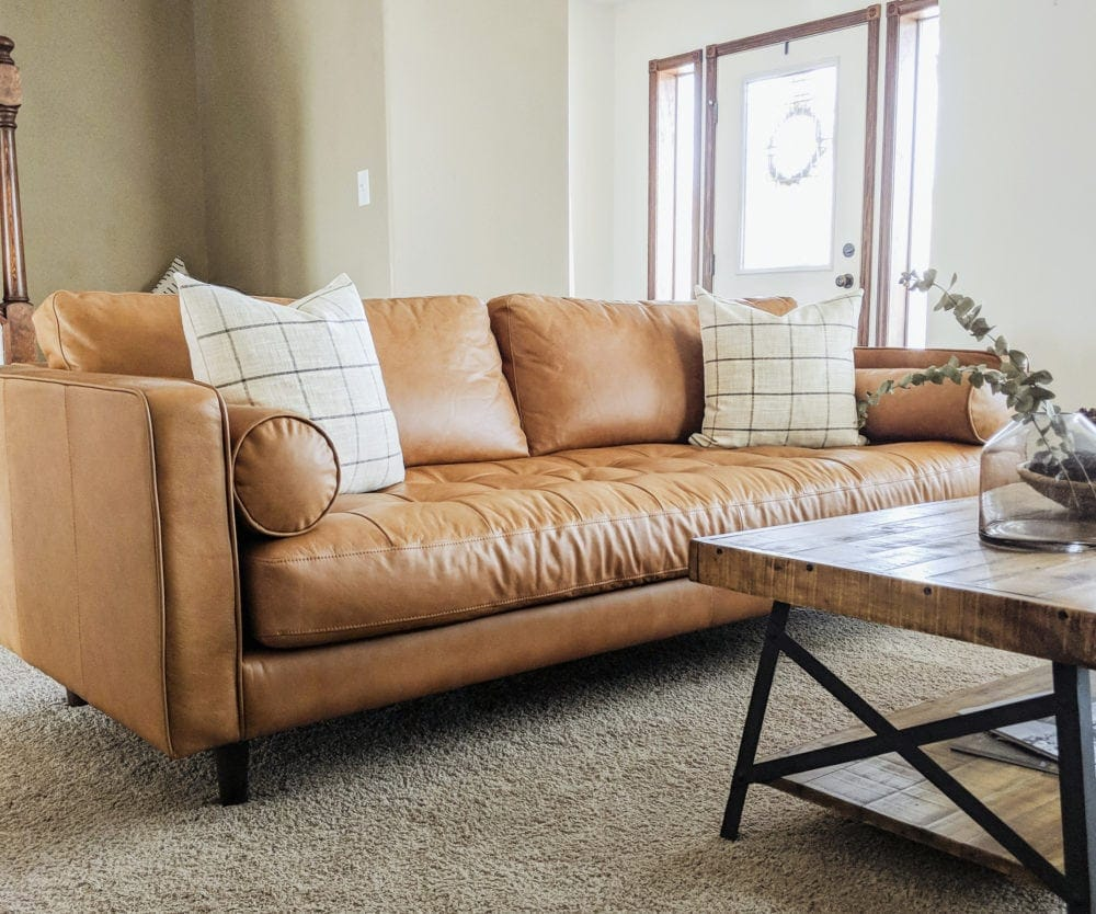 Tan leather sofa with two throw pillows in a living room