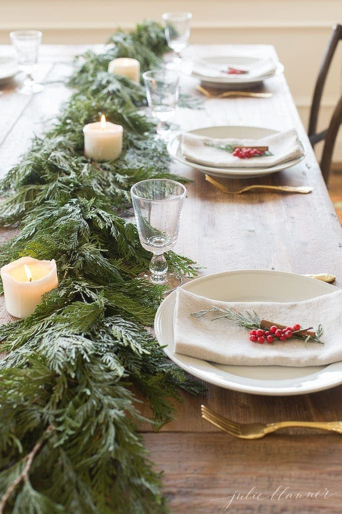 Simple christmas table setting ideas using holly berries, folded napkins and cinnamon sticks