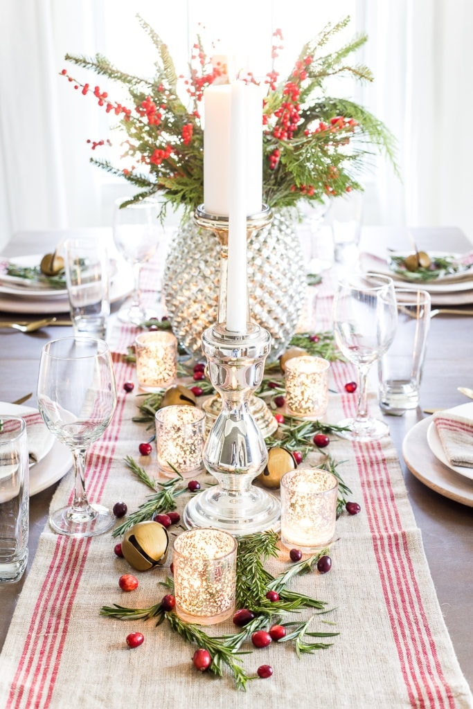 Christmas table centerpiece with votive candles and red striped runner
