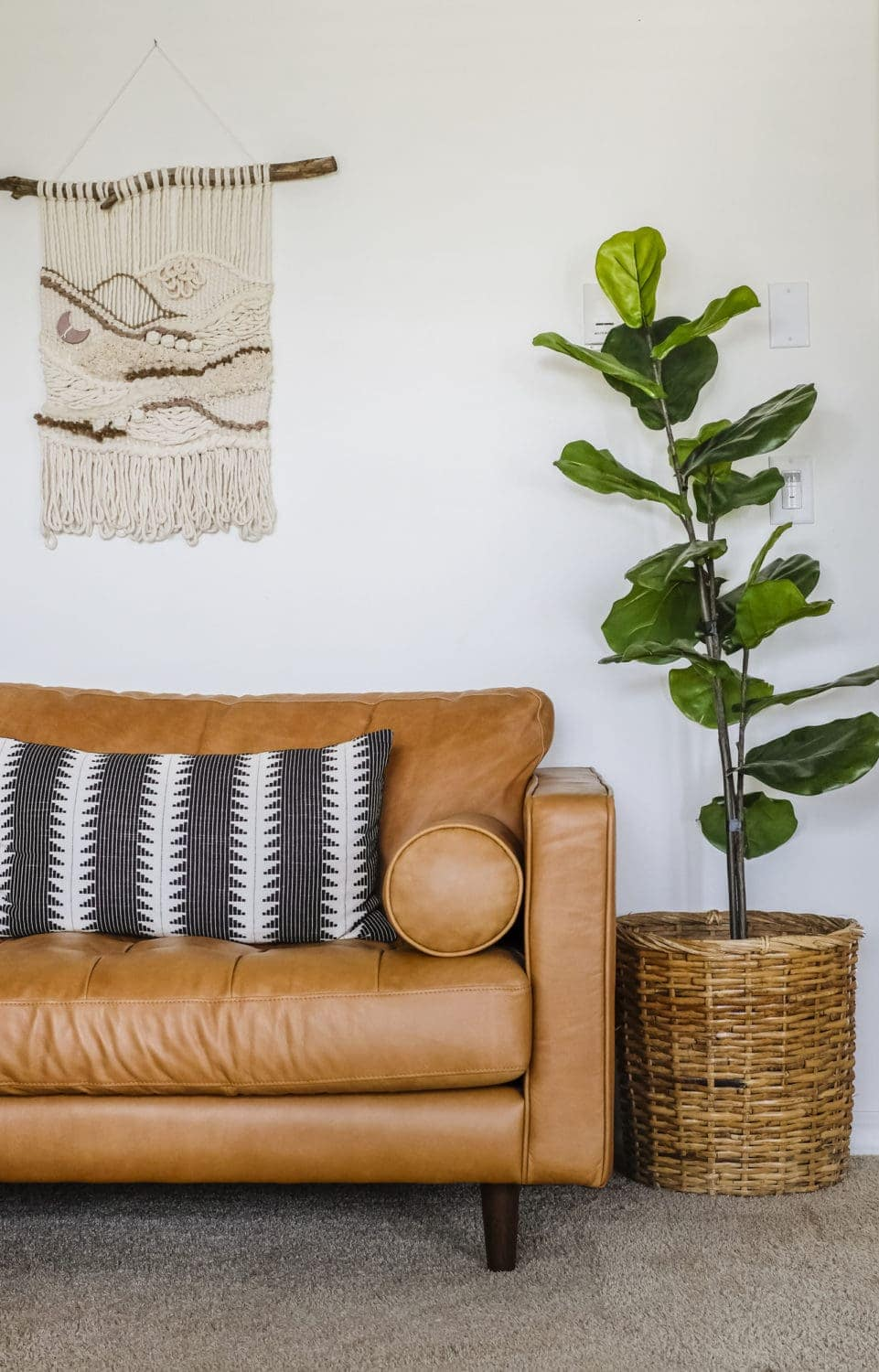 Leather sofa with black throw pillow next to an artificial fiddle leaf fig tree
