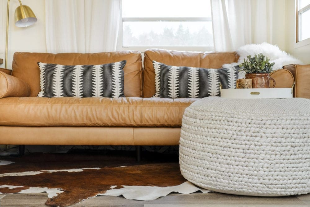a large fabric floor pouf in front of a leather sofa with a tray on top