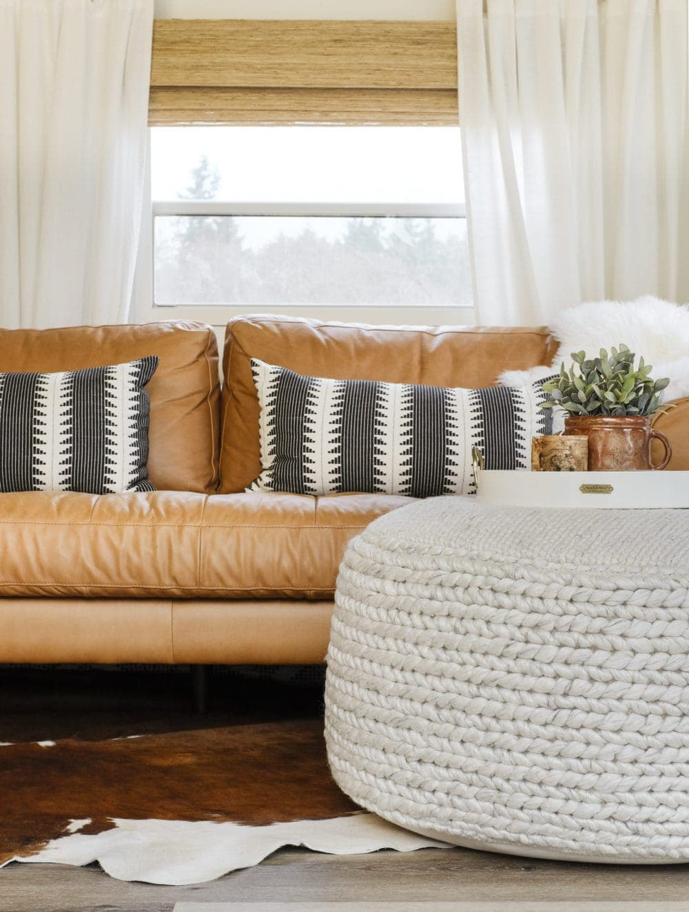 Floor pouf for living room in front of a leather sofa with a decorative tray on top