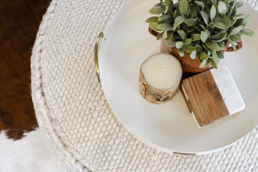 Overhead angle of a decorative tray that has a candle, greenery and coasters