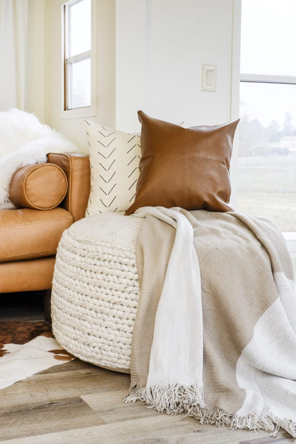 Large fabric pouf with two throw pillows and a blanket on top