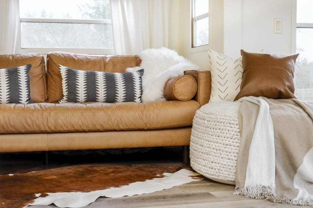 Large woven pouf for living room in front of a leather sofa with pillows and a blanket