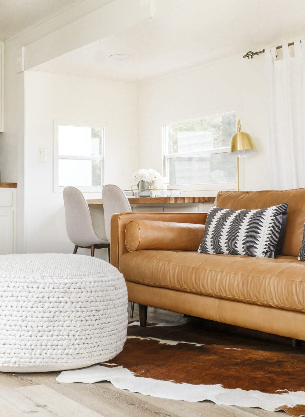 Large pouf in a small room in front of a brown leather couch