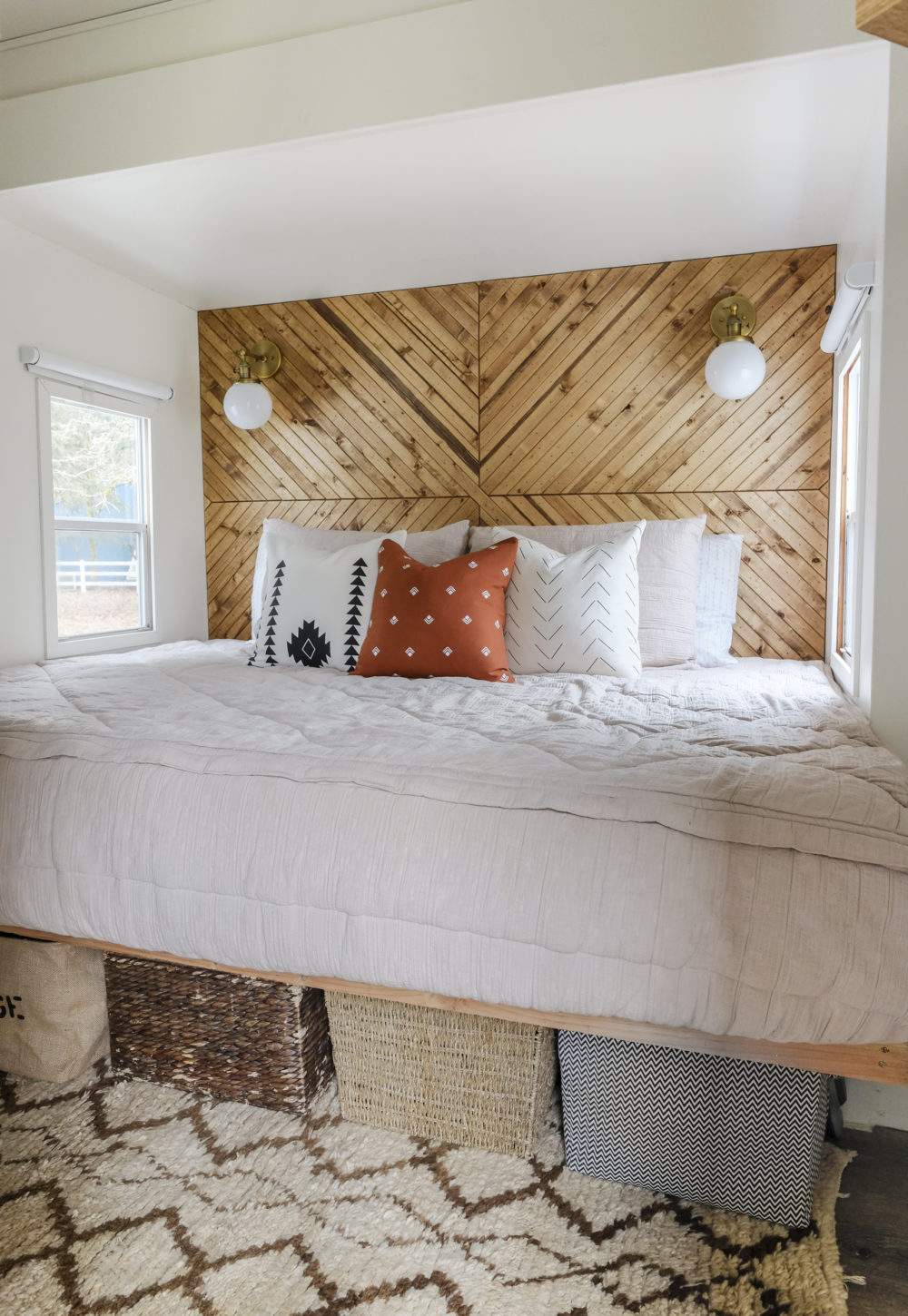 RV bedroom remodel with underbed storage and a geometric wood plank accent wall