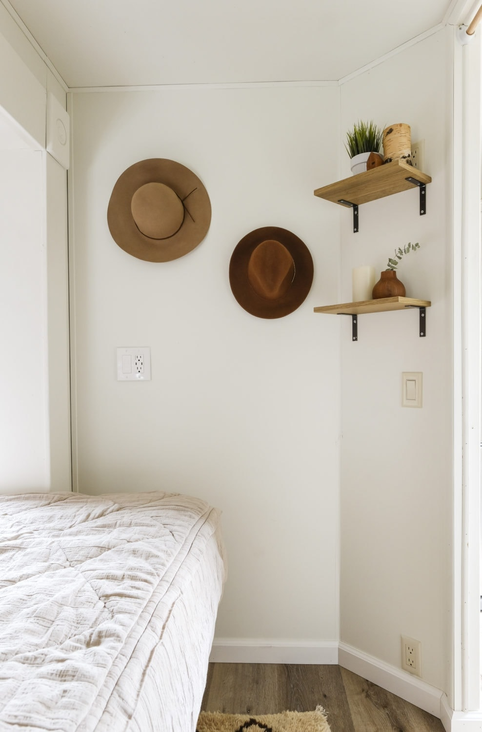 RV bedroom remodel with hats hanging on the wall and open shelving