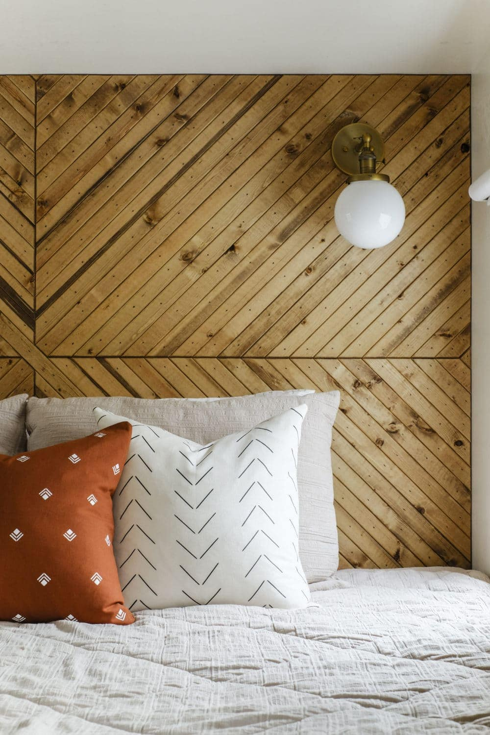 Closeup of wood plank accent wall behind bed and a brass wall sconce