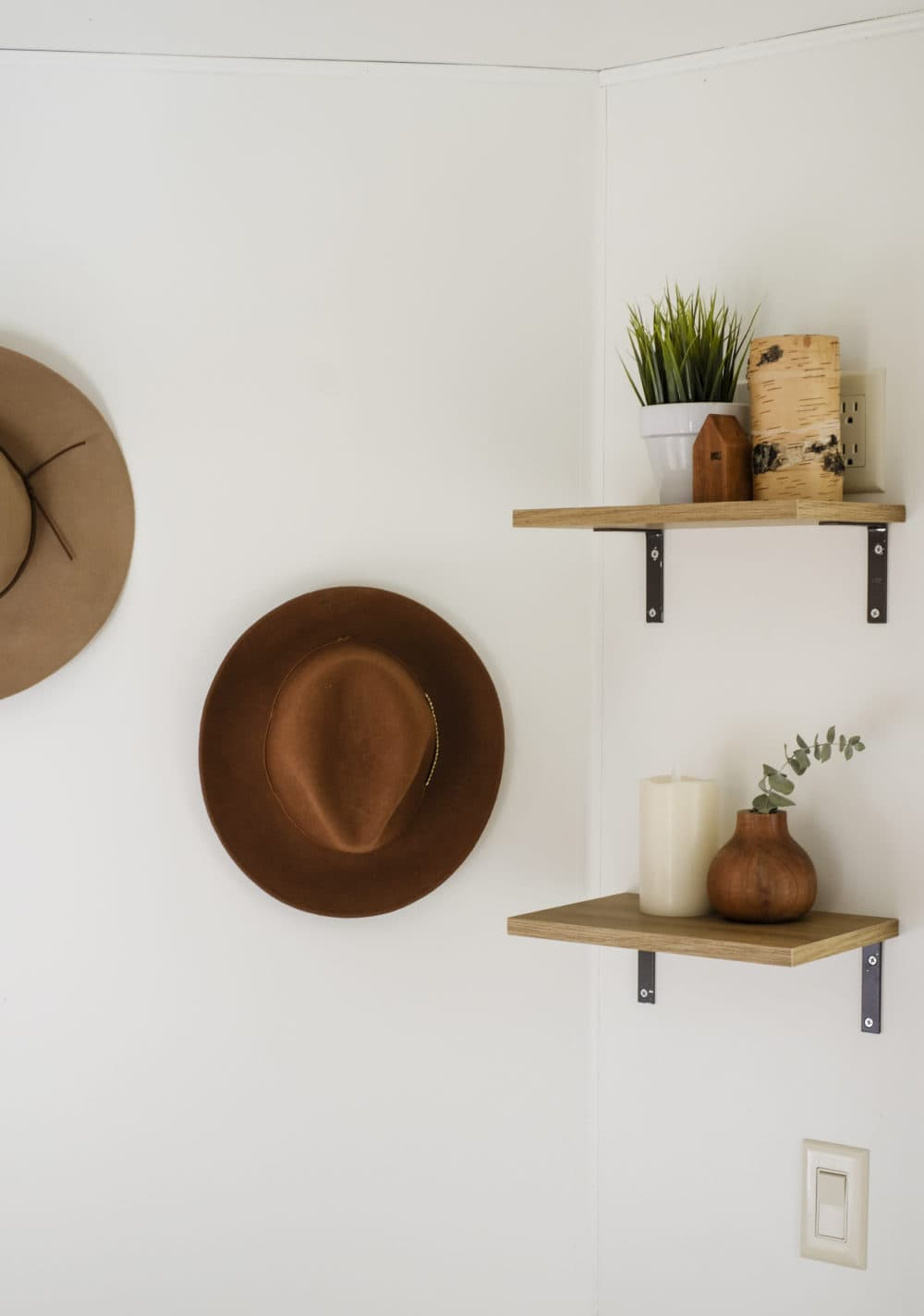 Open shelving on the wall and hats hung on a hook