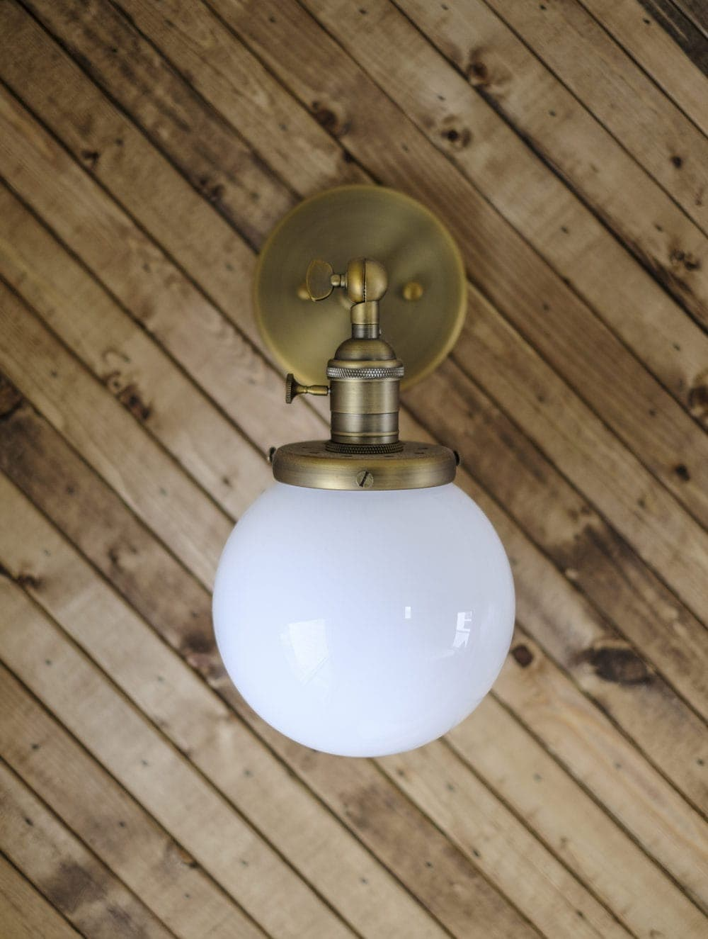 Brass wall sconce with globe light shade