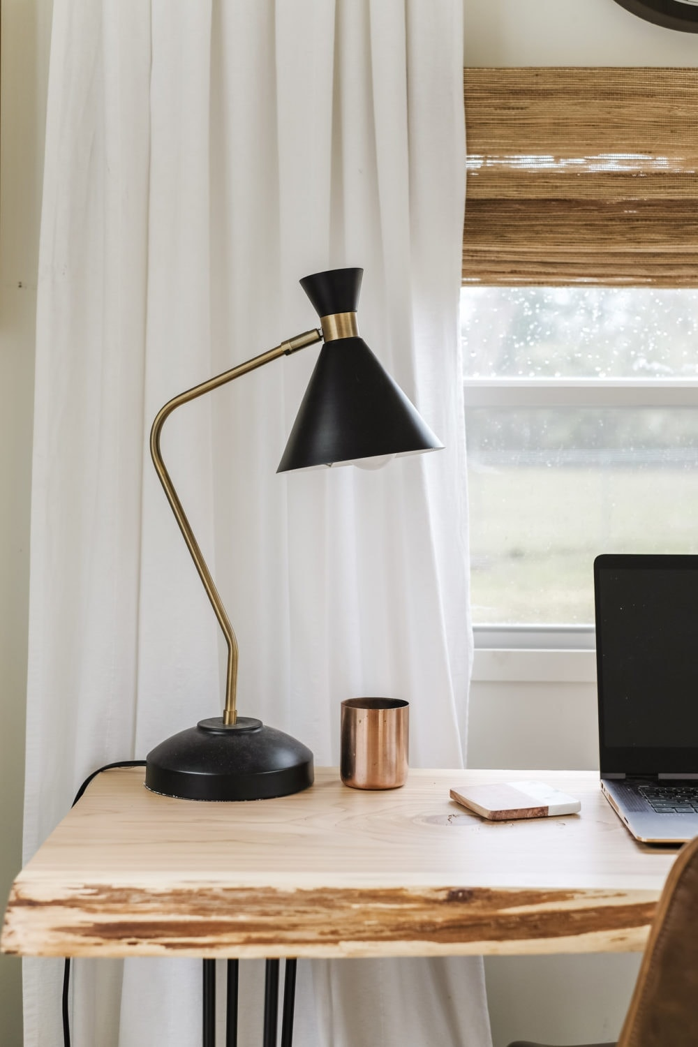 Black modern desk lamp and copper candle on top of wood desk