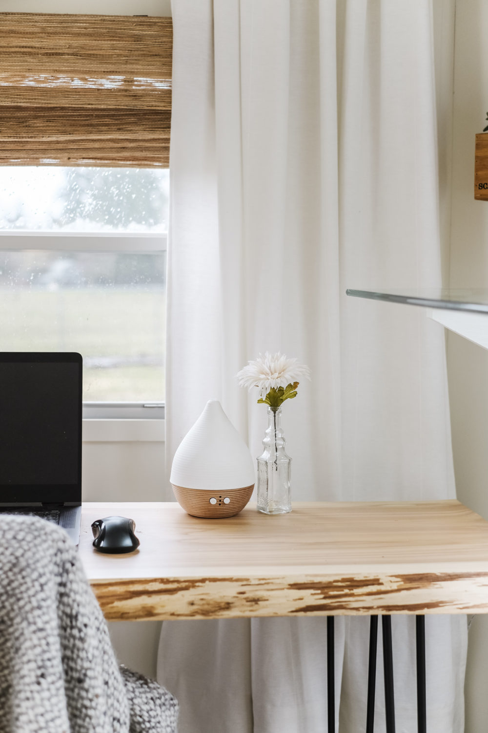 Modern oil diffuser and small vase on top of wood desk