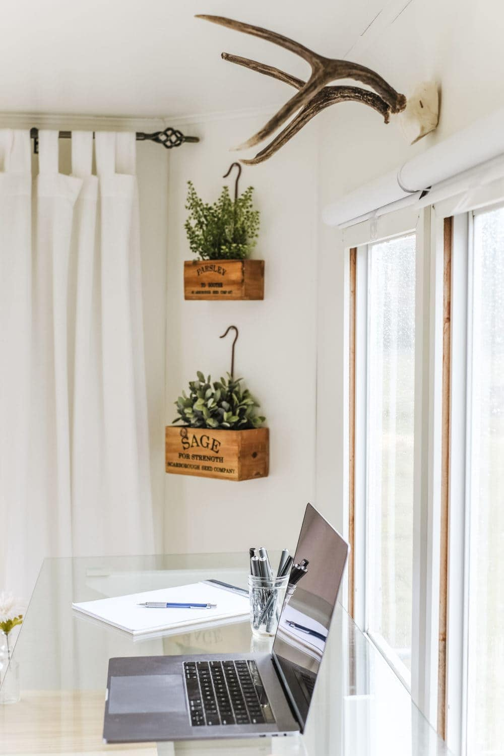 Home office with antlers on the wall and a laptop on a glass desktop