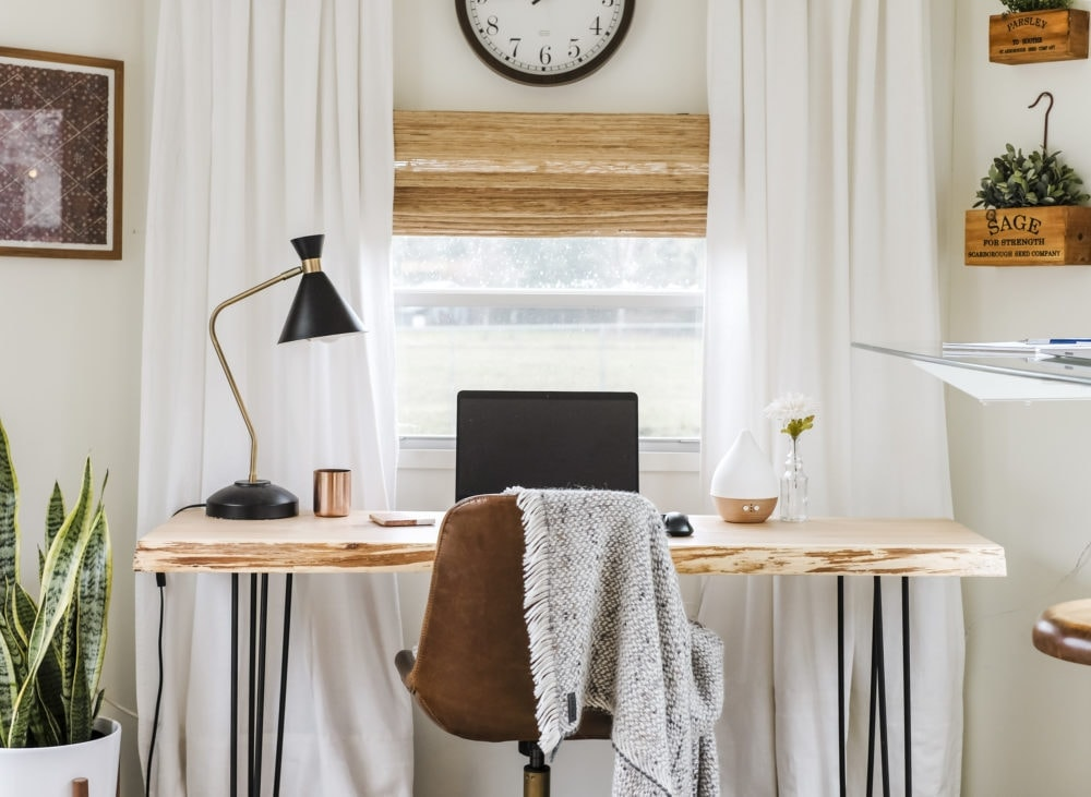 Home office inspiration with wood desk, leather chair and white curtains