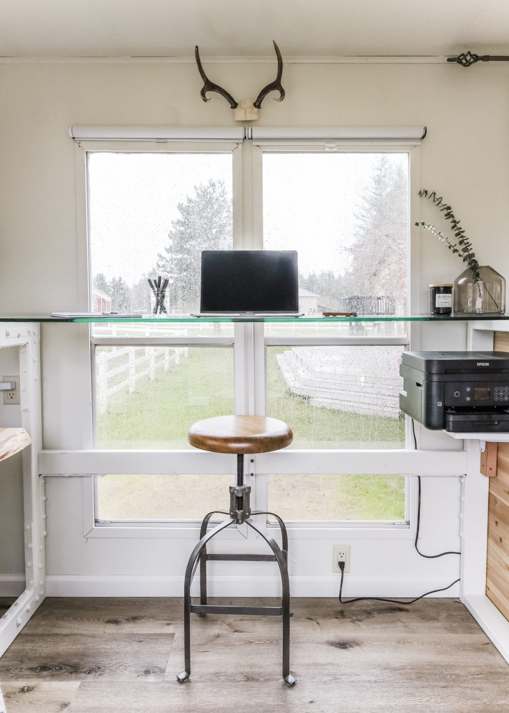 Standing desk with glass desk top in front of large windows