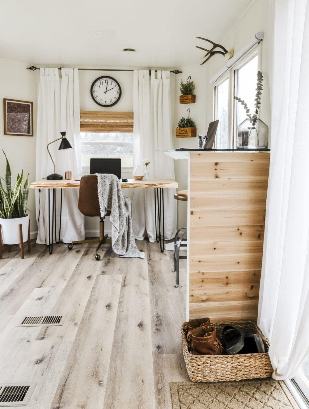 View of a home office next to an entry way with cedar planks and a shoe basket