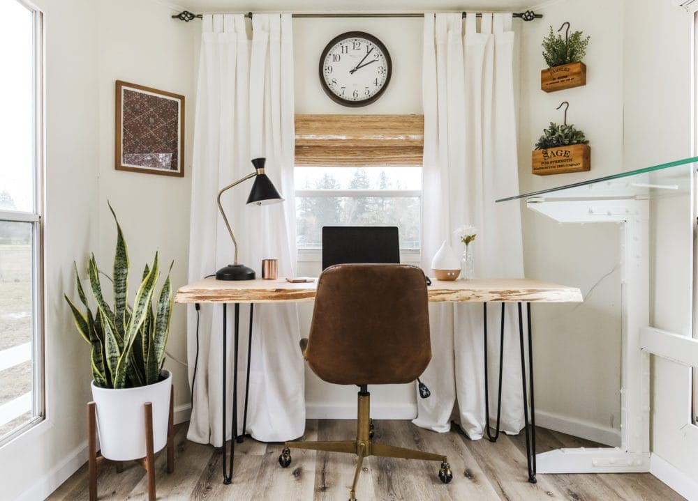 Light and bright home office inspiration with wood desk, snake plant and woven shades