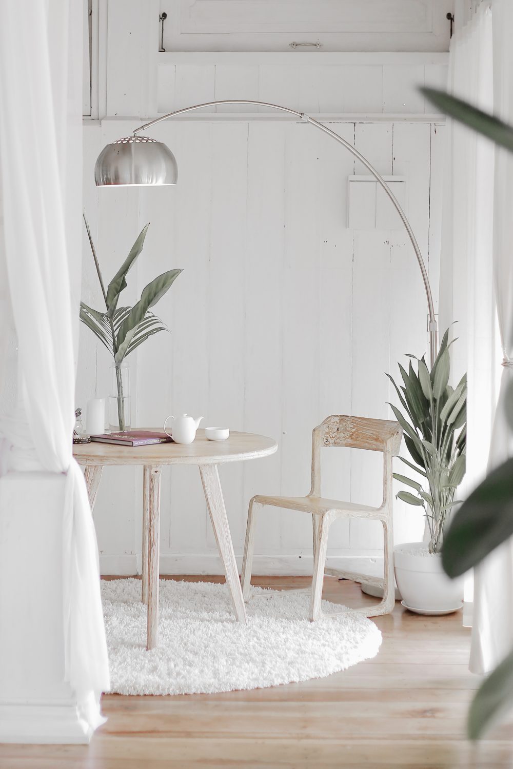coastal style decor with white walls, bleached wood furniture and beachy greenery