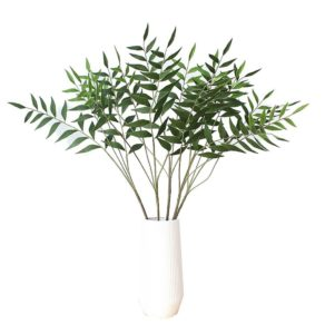 artificial eucalyptus branches inside a white vase