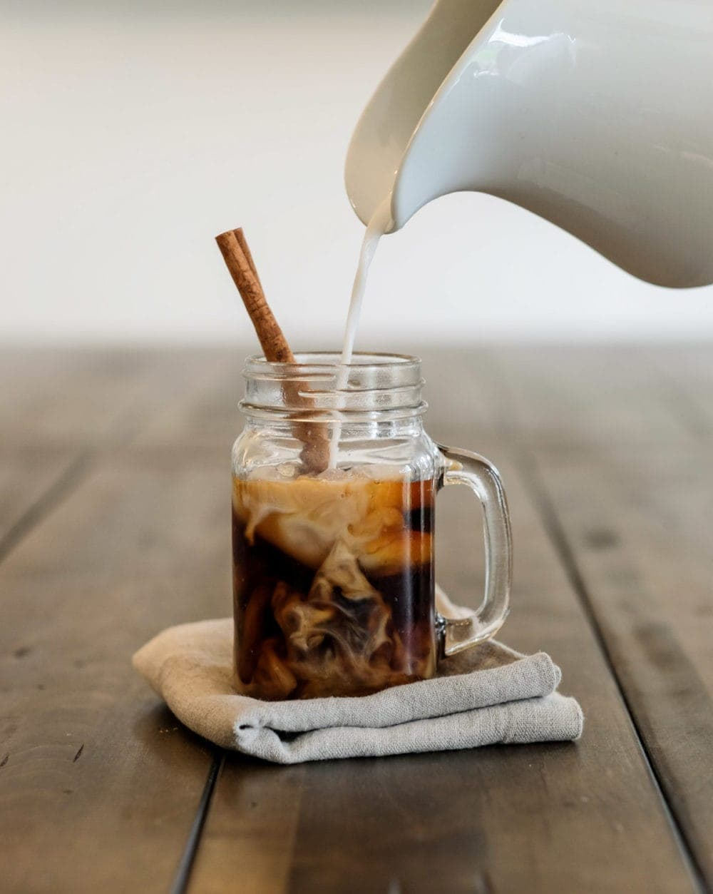 pouring cream into cold brew coffee