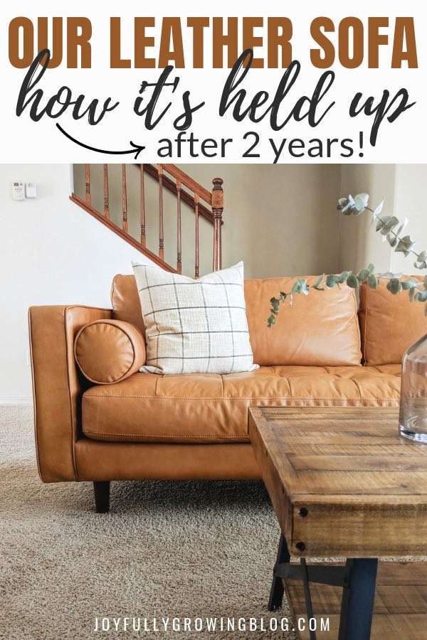 "Leather sofa with white throw pillow and text overlay that reads ""Our leather sofa, how its held up after 2 years!"""