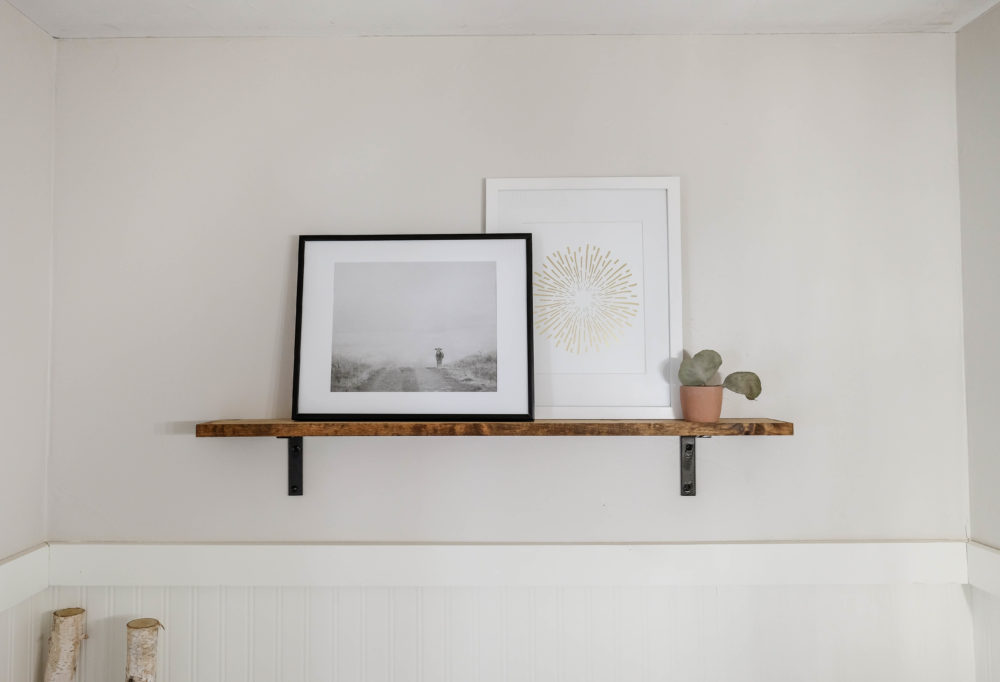 framed prints on an open shelf on a white wall